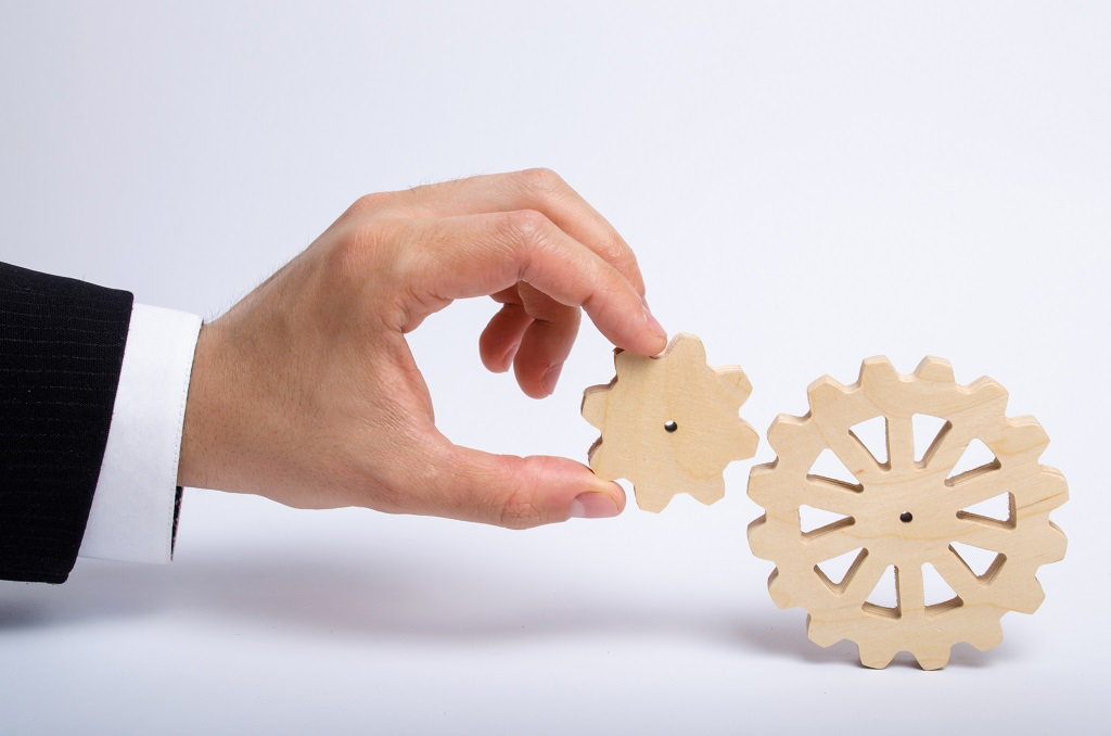 Hand Of Businessman In Suit Holds The Gear To Another Gear Wheel. The Hand Connects Two Round Gears. The Concept Of Business Processes And Ideas, Building A Career And Carrying Ideas. Innovations.