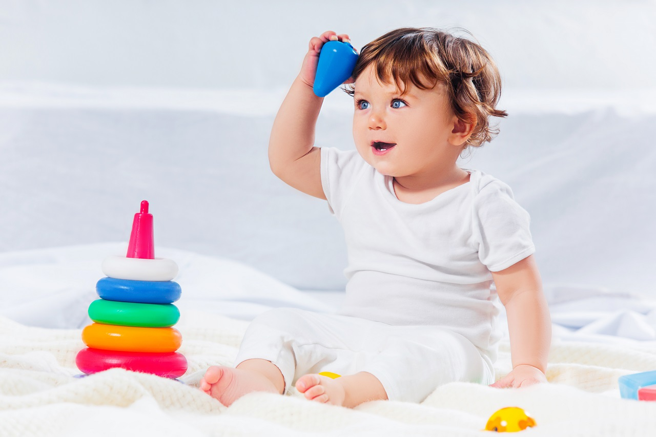 a baby boy sitting on the floor playing with plastic ring toys