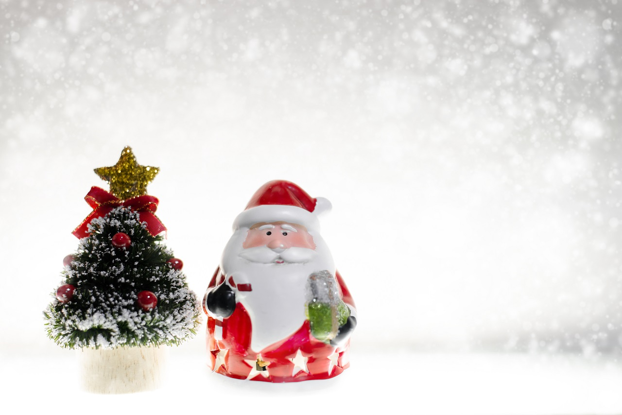 A small plastic santa claus beside a christmas tree