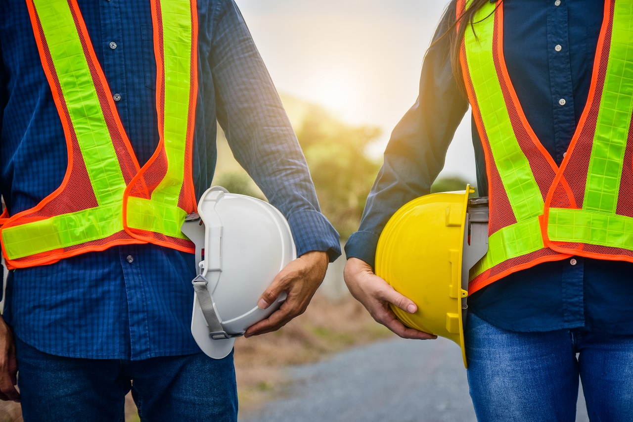 Two construction workers holding their plastic hardhats