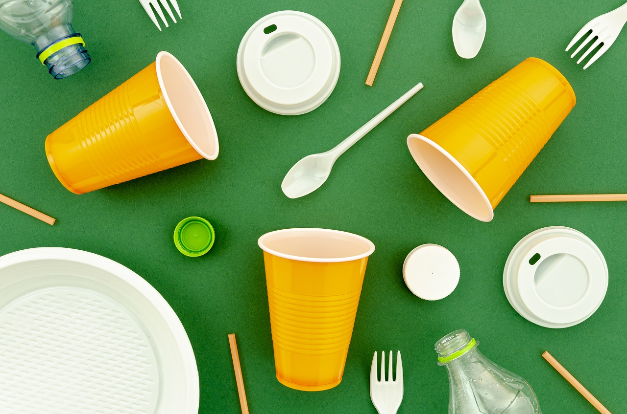 Plastic cups, covers, and utensils on a green background