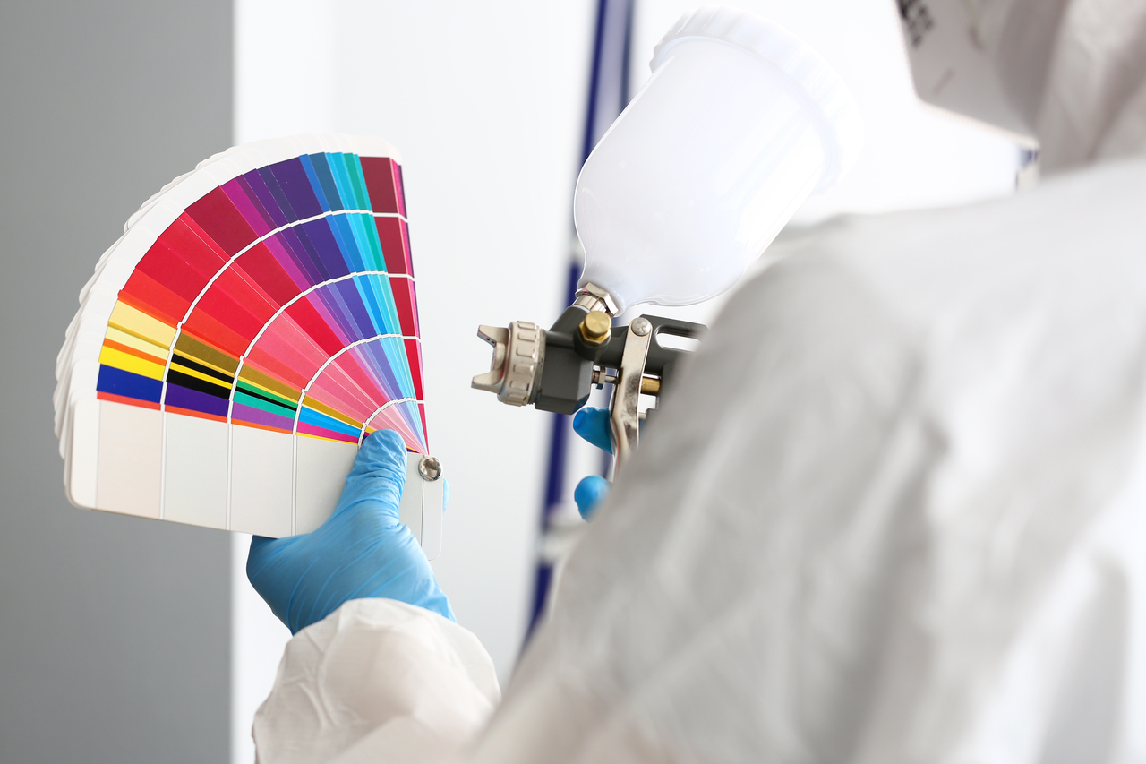 A person holding a spray paint and a color wheel