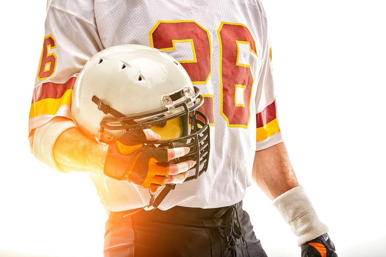 A footballer holding his plastic helmet