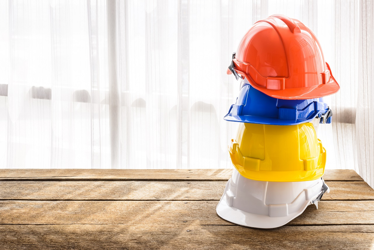 Four plastic hardhats stacked on top of each other on a table
