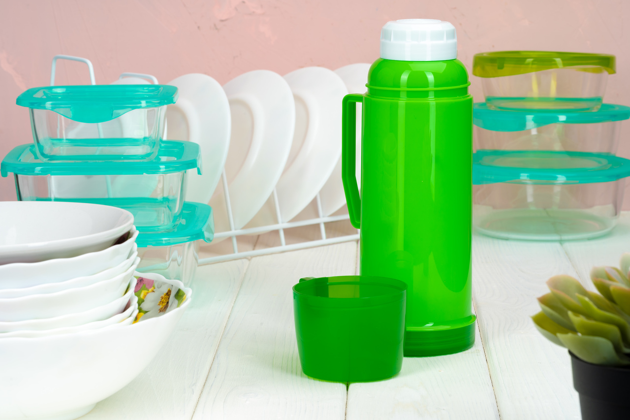 A green plastic thermos in a kitchen
