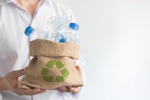 A man holding a bag of plastic bottles for recycling